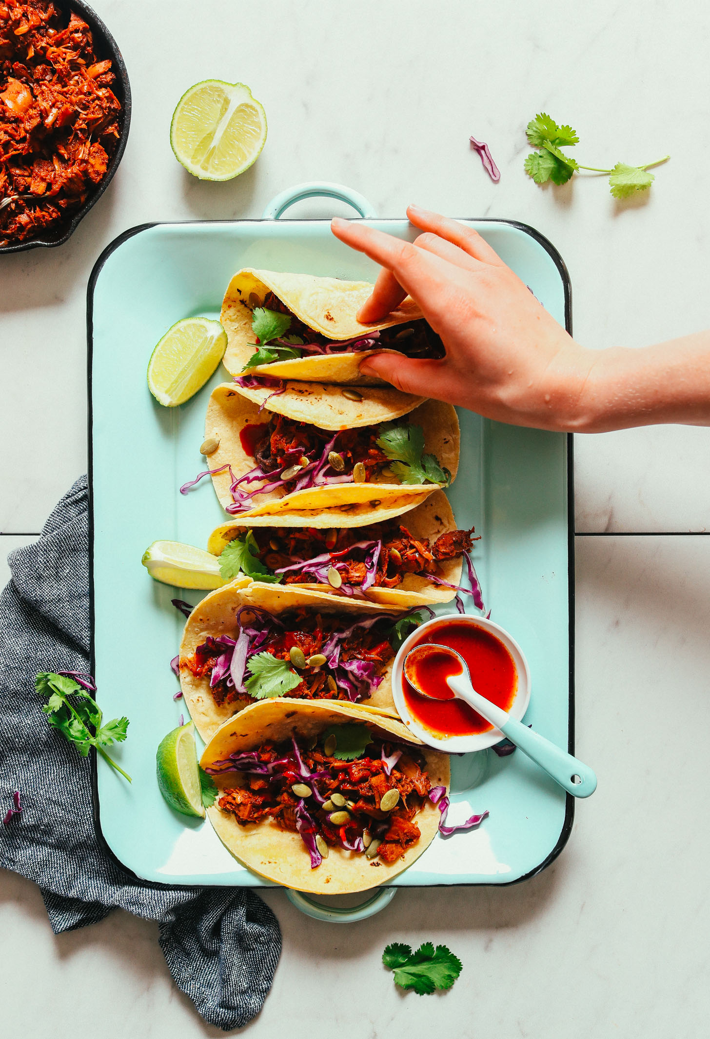 Grabbing a gluten-free vegan Jackfruit Taco from a platter