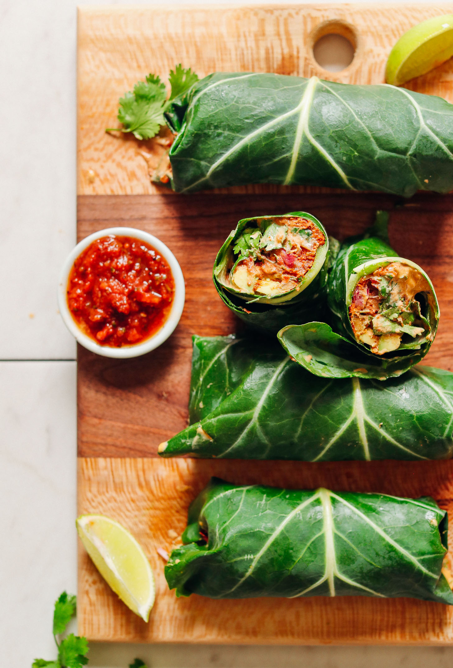 Batch of our Raw Vegan Burritos recipe on a wood cutting board with salsa and lime for serving
