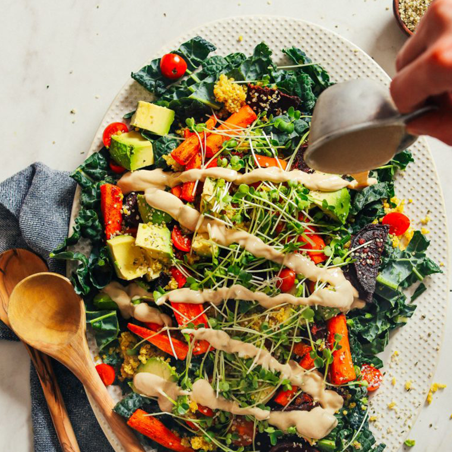 Drizzling dressing onto a salad for our Best Plant-Based Lunch Recipes roundup