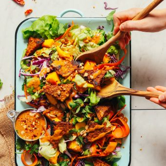 Using salad tongs to grab a serving of Healthy Mango Green Salad with Creamy Peanut Dressing