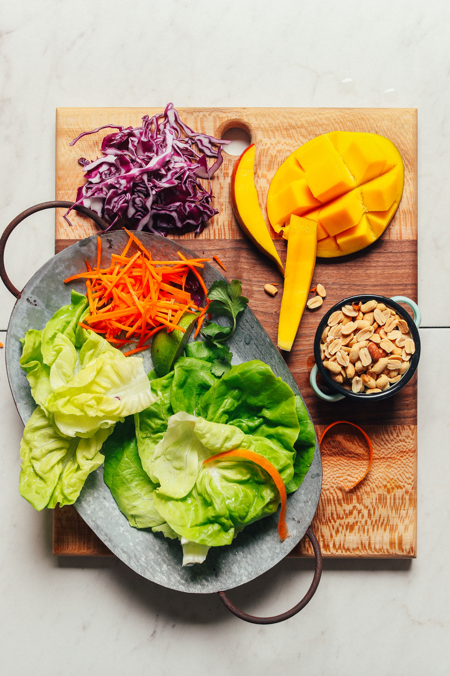 Cutting board with lettuce, carrots, red cabbage, mango, and peanuts for making a healthy vegan salad