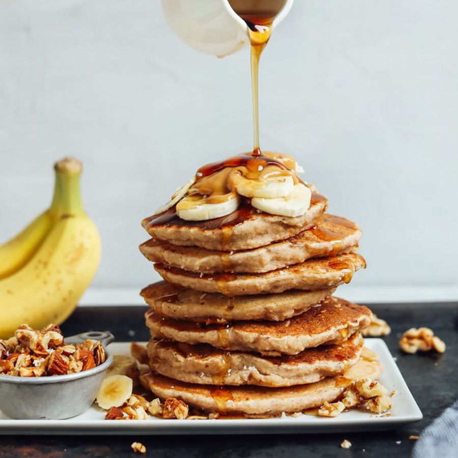 Pouring syrup onto a stack of pancakes as part of our Best Vegan Breakfast Recipes roundup