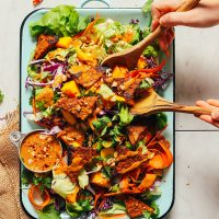 Using wooden salad spoons to grab a serving of our colorful Mango Salad with Peanut Dressing