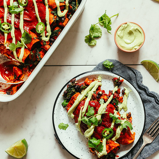 Plate and baking dish filled with our vegan Sweet Potato Black Bean Enchiladas