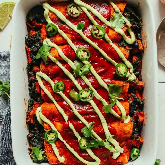 Ceramic baking dish filled with gluten-free vegan Enchiladas drizzled with avocado crema
