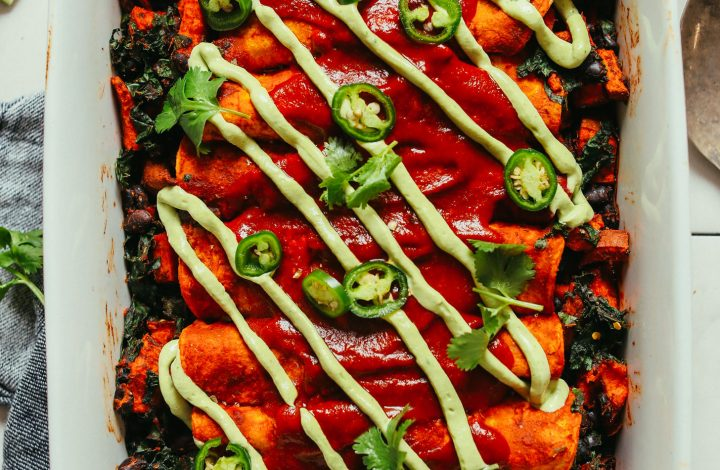 Ceramic baking dish filled with gluten-free vegan Enchiladas drizzled with avocado crema