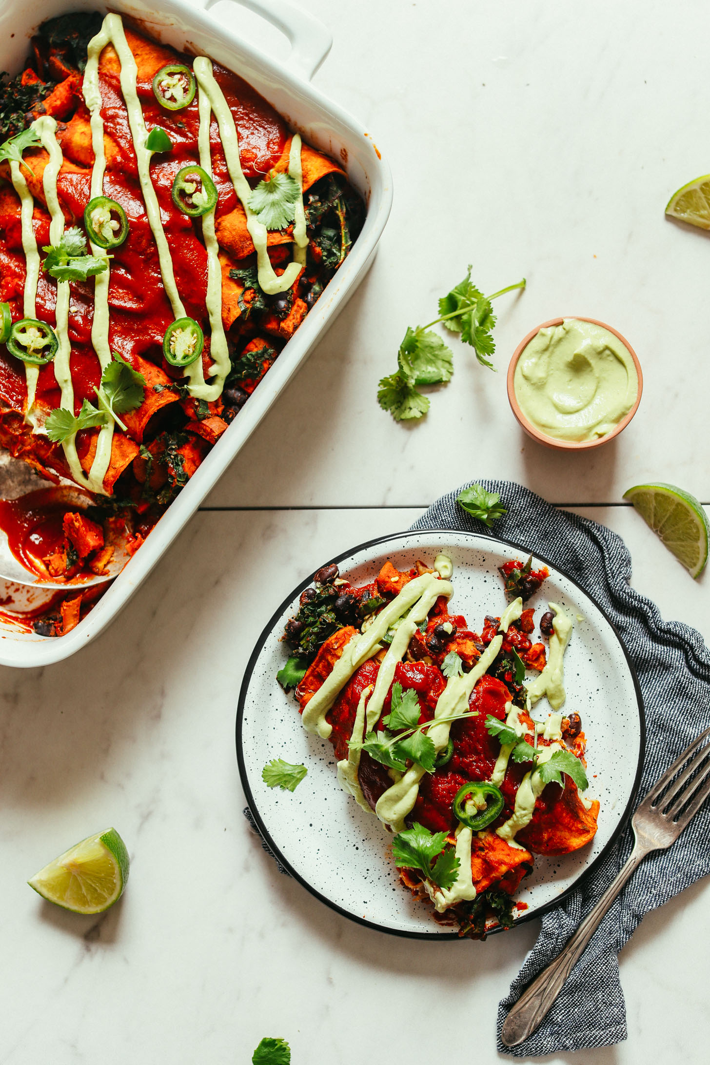 Baking pan and plate full of gluten-free vegan Sweet Potato Black Bean Enchiladas