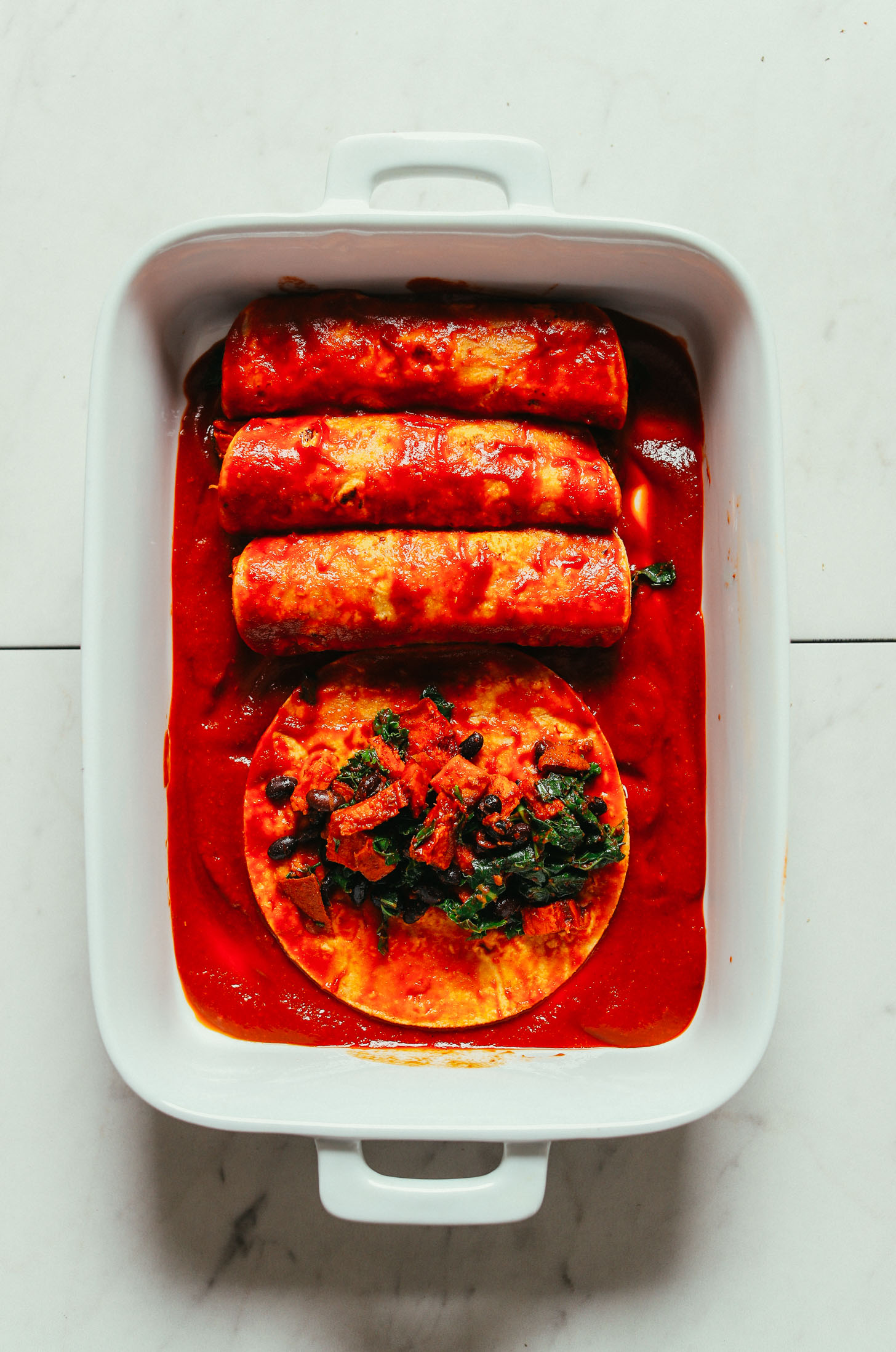 Rolling up Sweet Potato Black Bean Enchiladas in homemade sauce in a baking dish