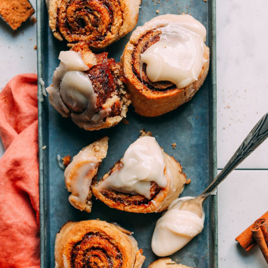 Spoonful of icing on a tray of Gluten-Free Cinnamon Rolls for our Vegan Desserts roundup