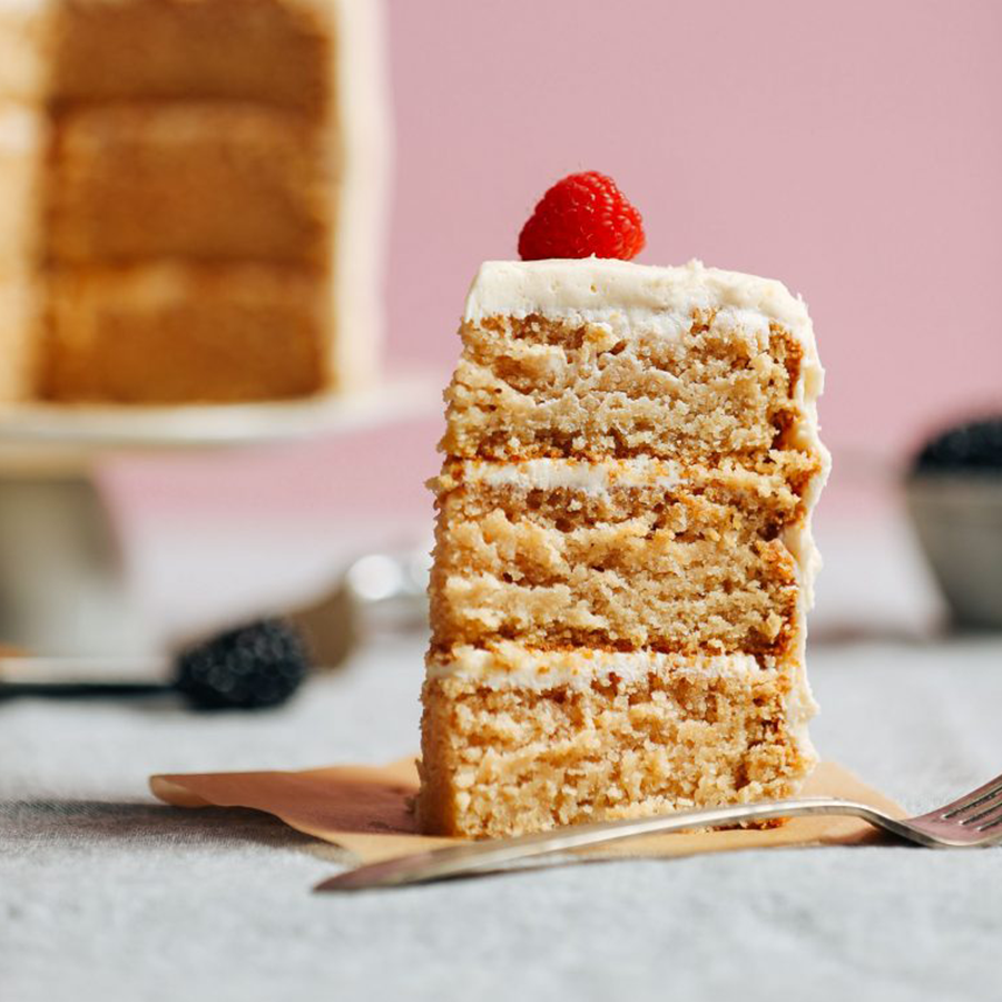 Slice of triple layer gluten-free vanilla cake for our roundup of the Best Vegan Desserts