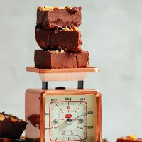 Slices of our 4-Ingredient Freezer Fudge recipe stacked on a vintage scale