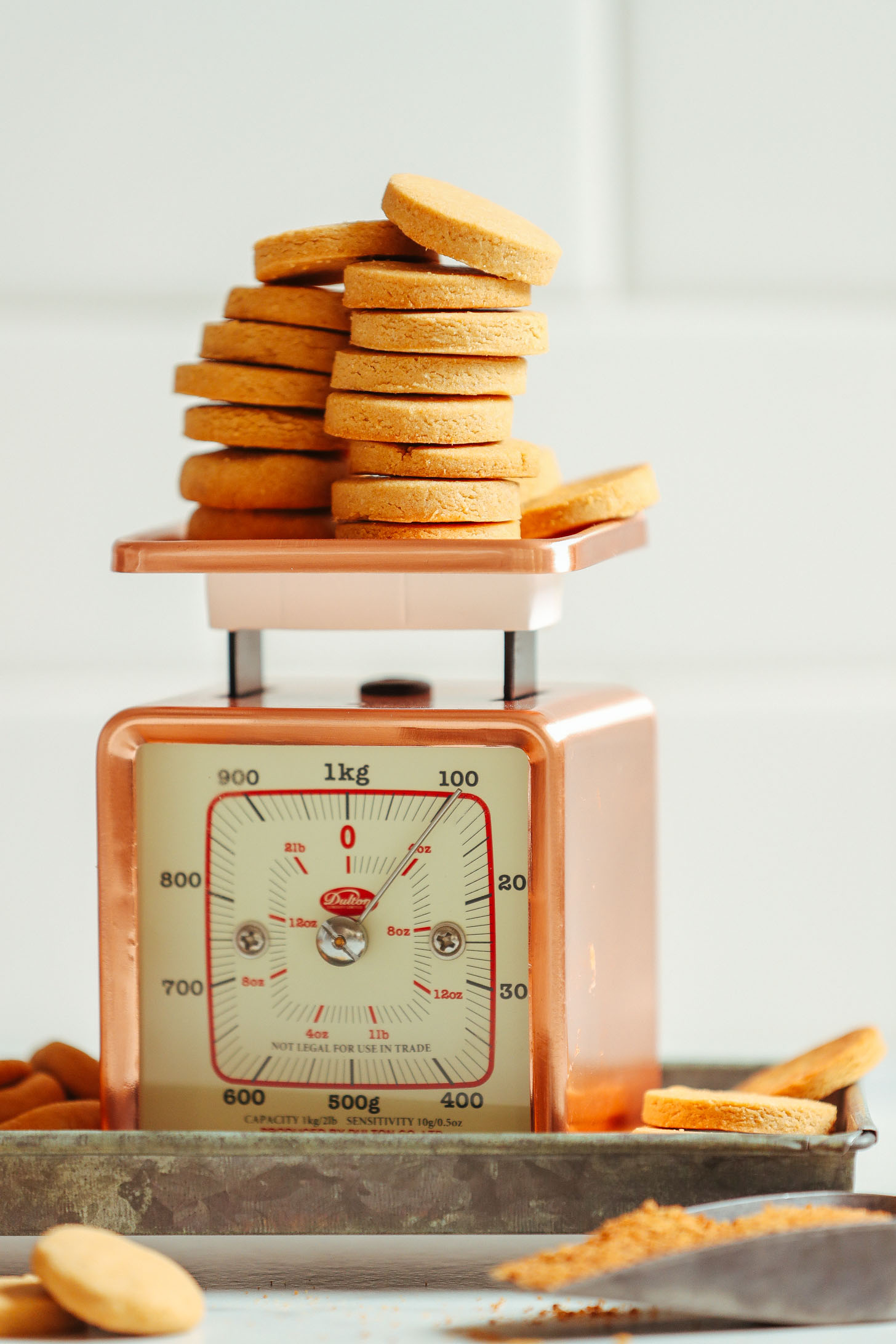 Stacks of sweet and crisp Vegan Gluten Free Vanilla Wafers perched on a vintage scale