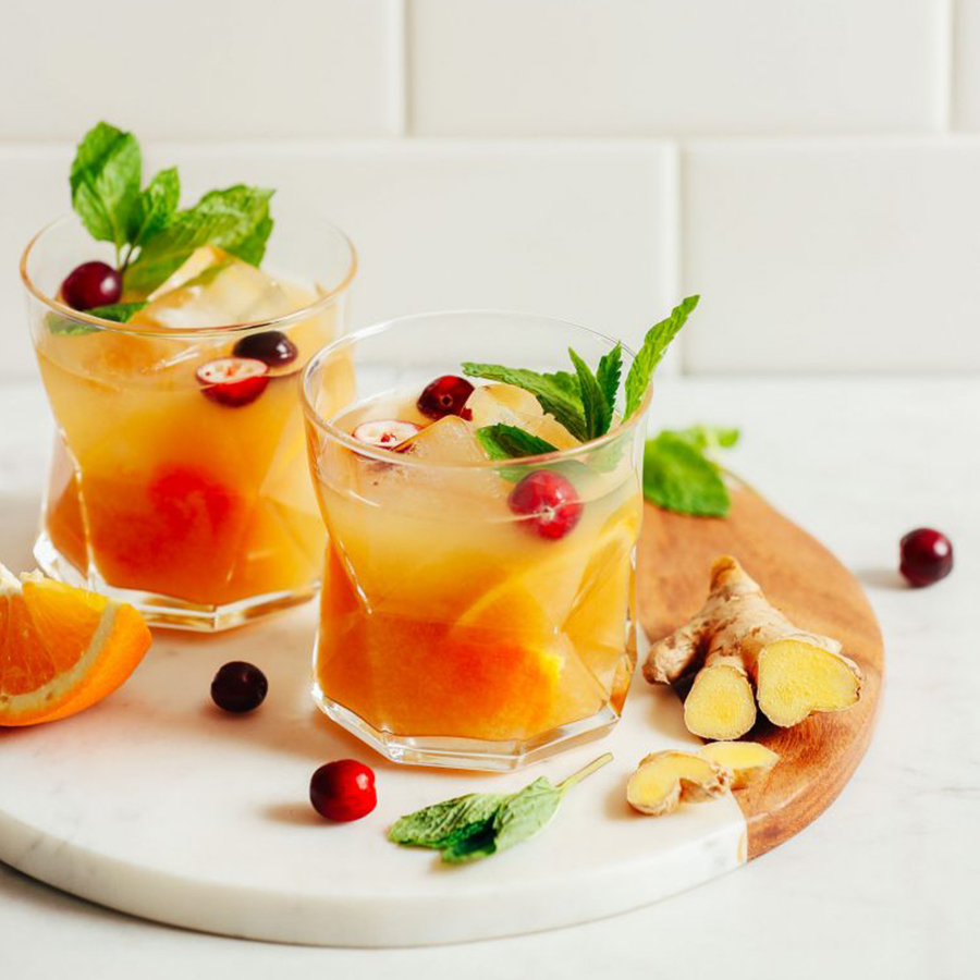Two glasses of our Orange Whiskey Ginger recipe garnished with fresh cranberries and mint