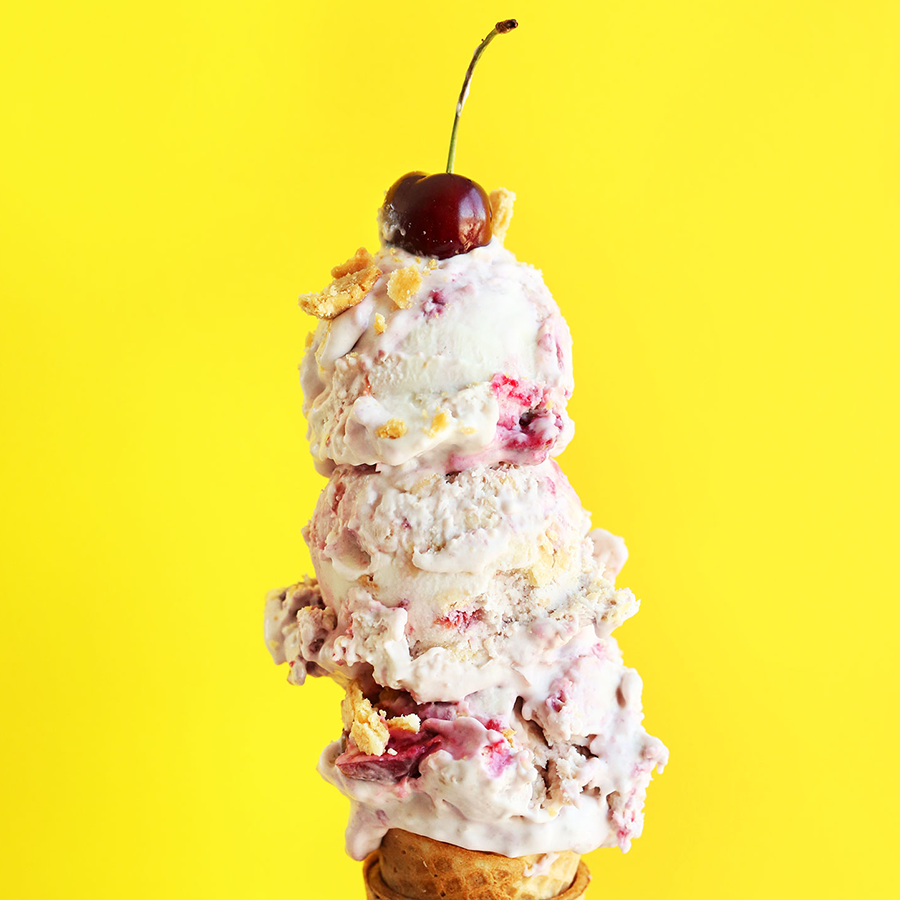 Triple scooped Vegan Cherry Pie Ice Cream on a sugar cone