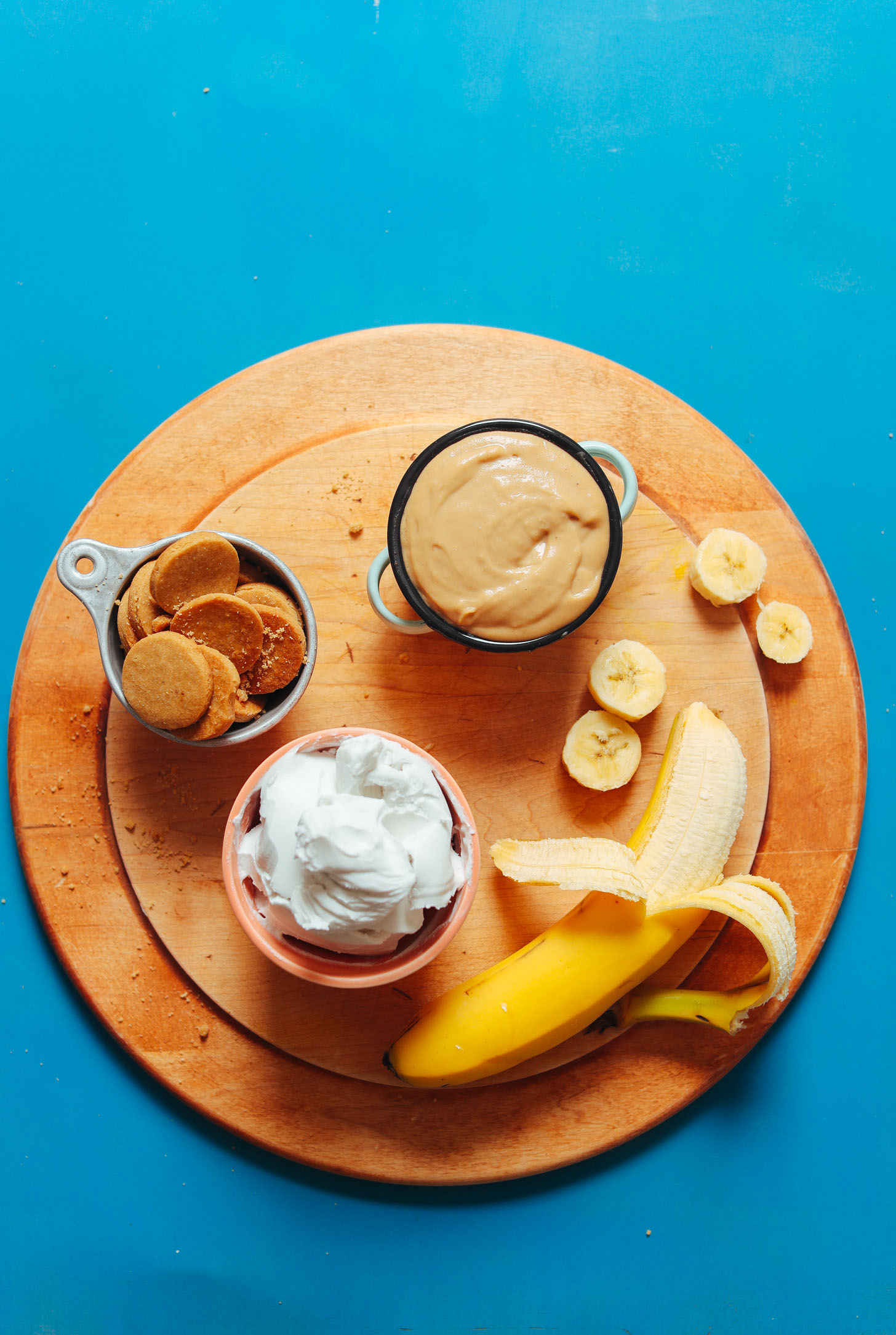Cutting board with banana, coconut whip, peanut butter pudding, and vanilla wafers for a delicious gluten-free vegan dessert