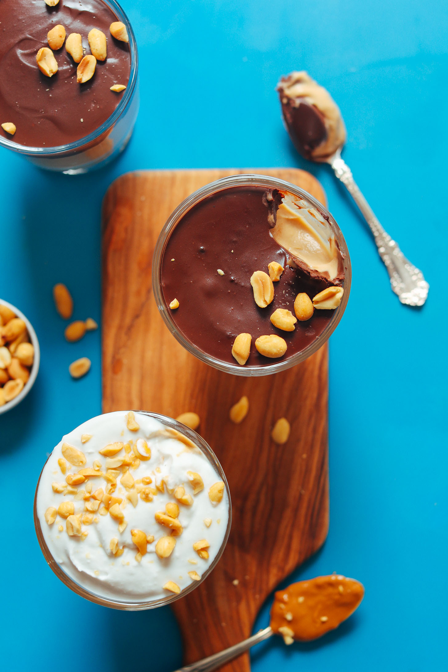 Glasses of Vegan Peanut Butter Pudding topped with chocolate ganache or coconut whip