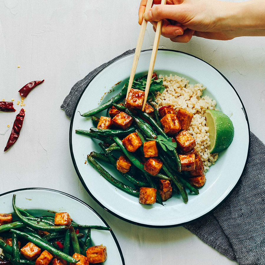 Using chopsticks to pick up a bite of stir fry for our Best Tofu Recipes roundup