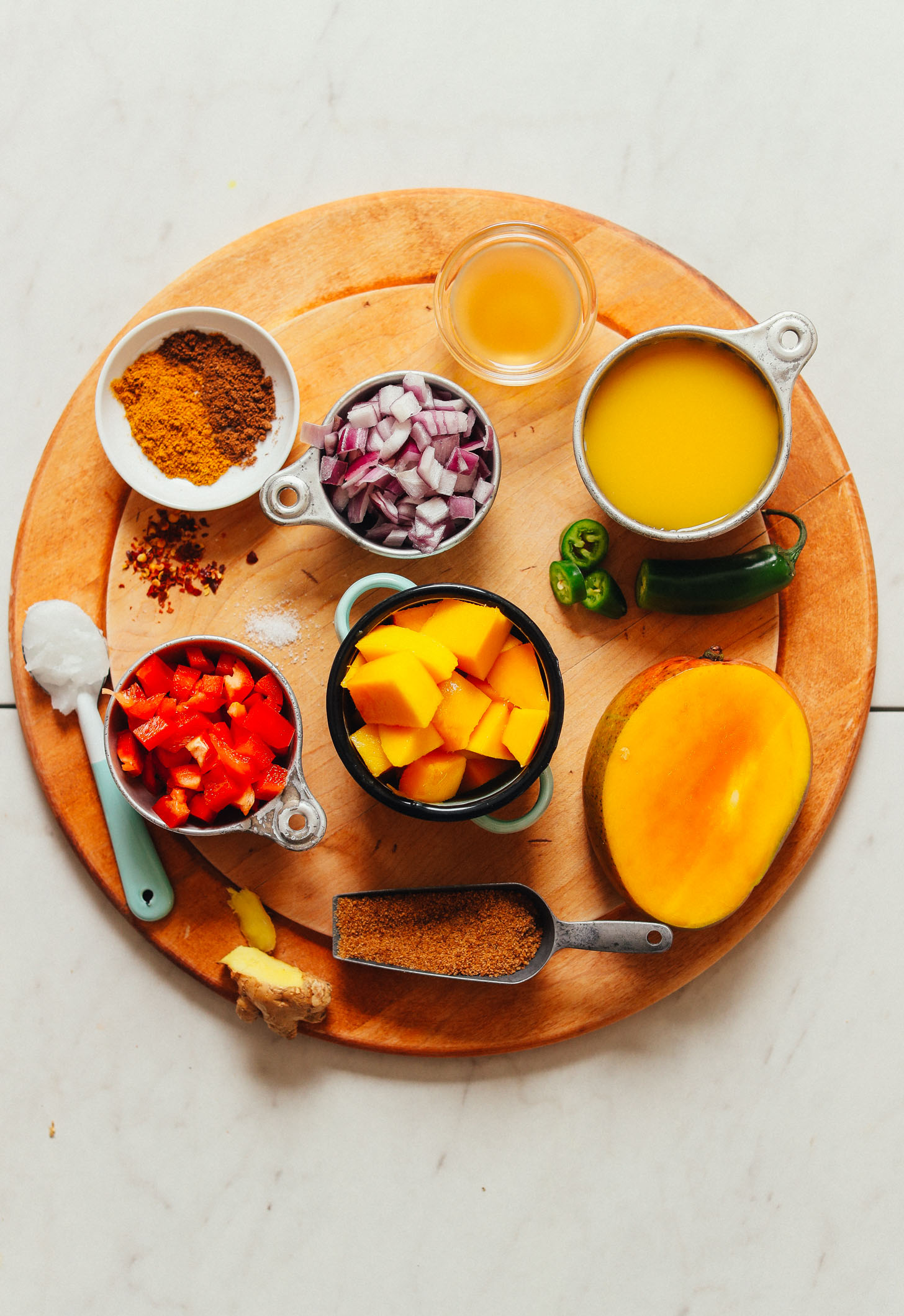 Wood cutting board filled with ingredients for making vegan Spicy Mango Chutney