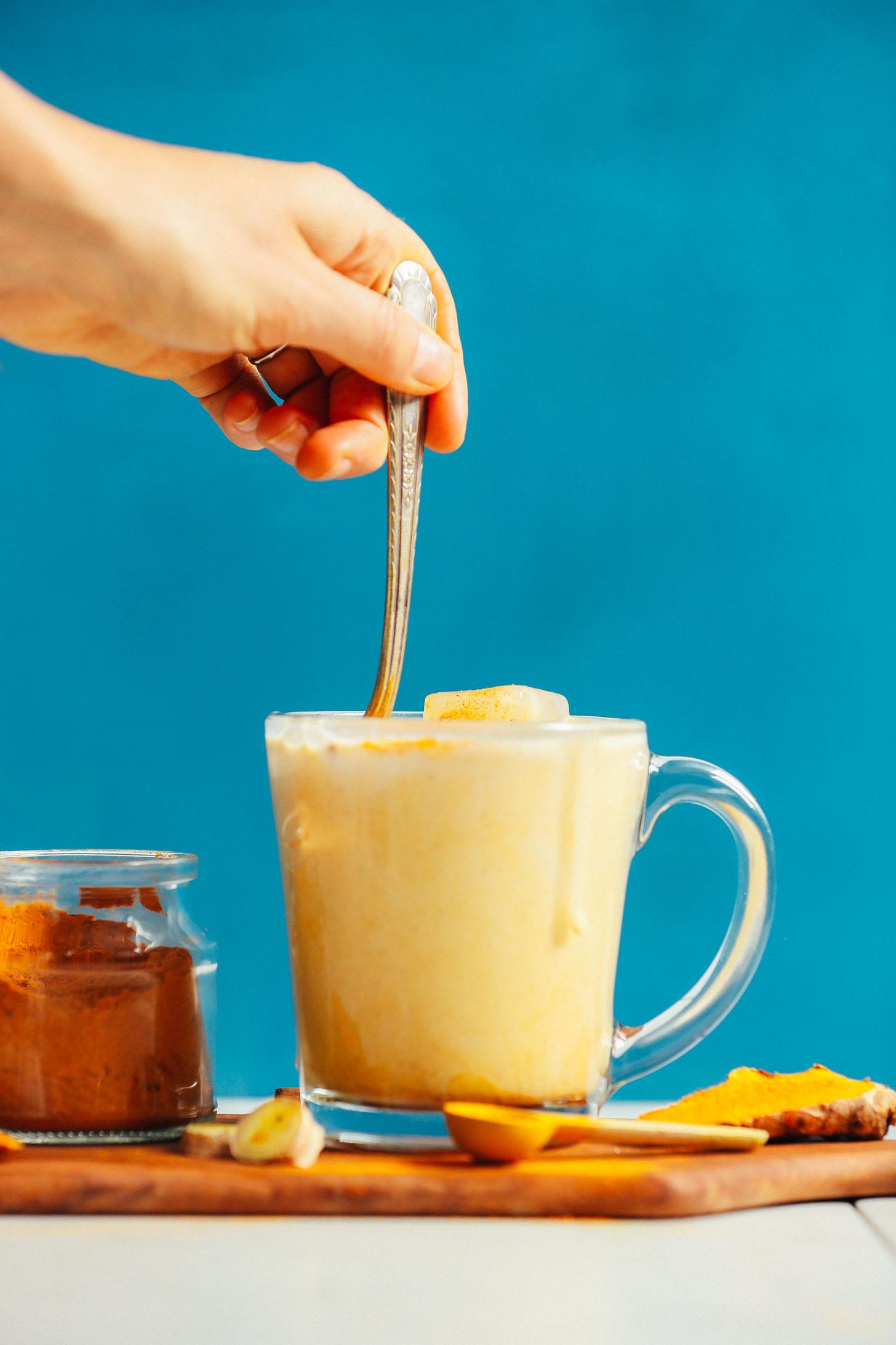Stirring a glass mug of delicious vegan iced golden milk