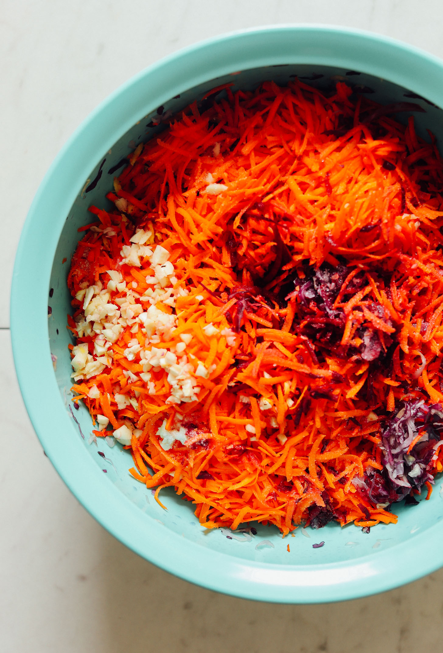 Big bowl of massaged cabbage, shredded carrots, and chopped garlic