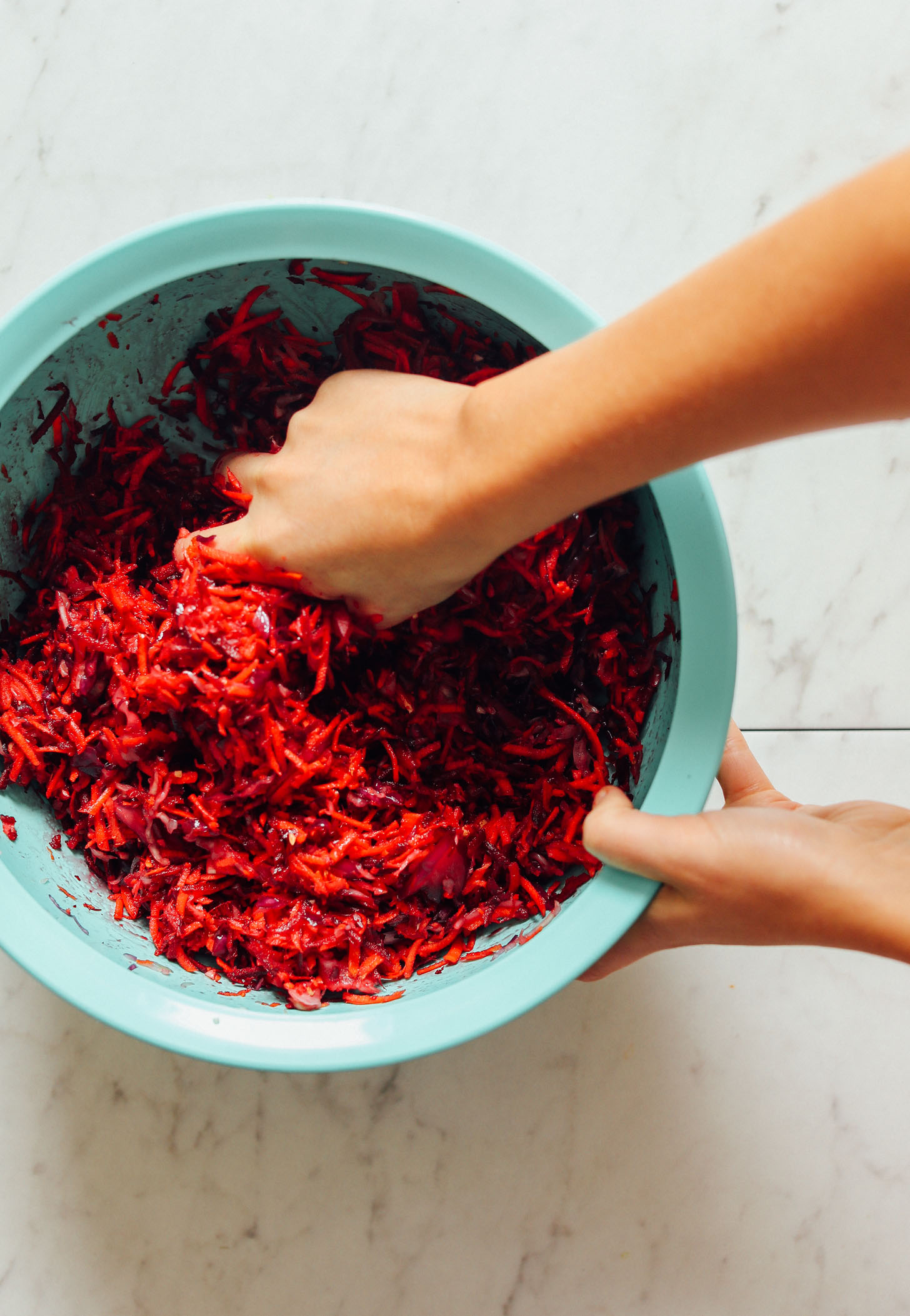 Massaging beets, carrots, and cabbage for our tutorial on How to Make Sauerkraut