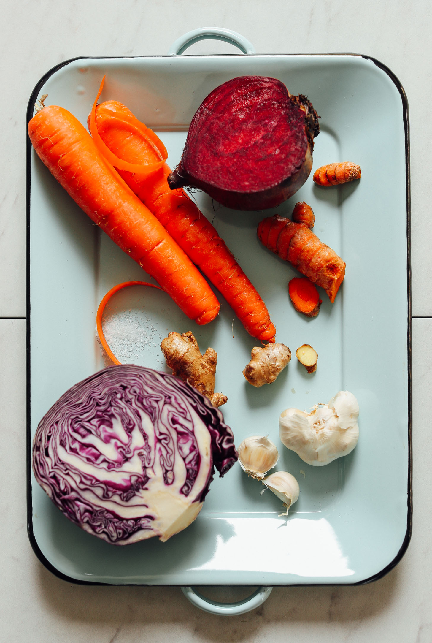 Tray of red cabbage, garlic, ginger, turmeric, carrots, and beets