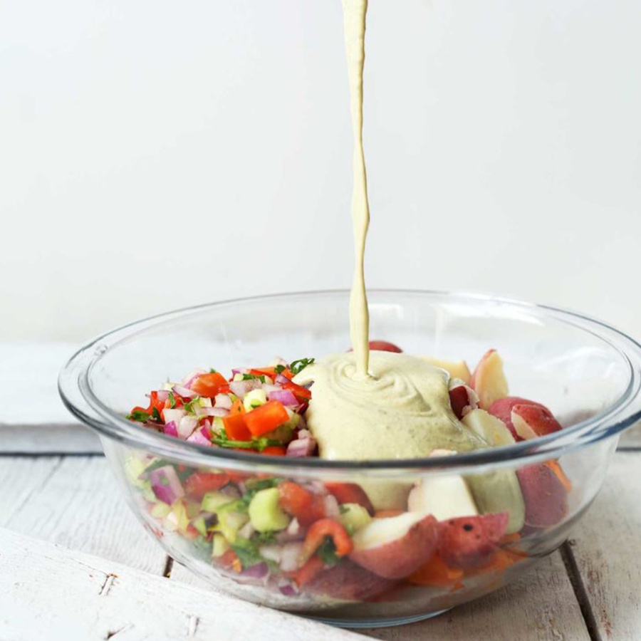 Pour dressing onto a bowl of our Simple Vegan Potato Salad recipe