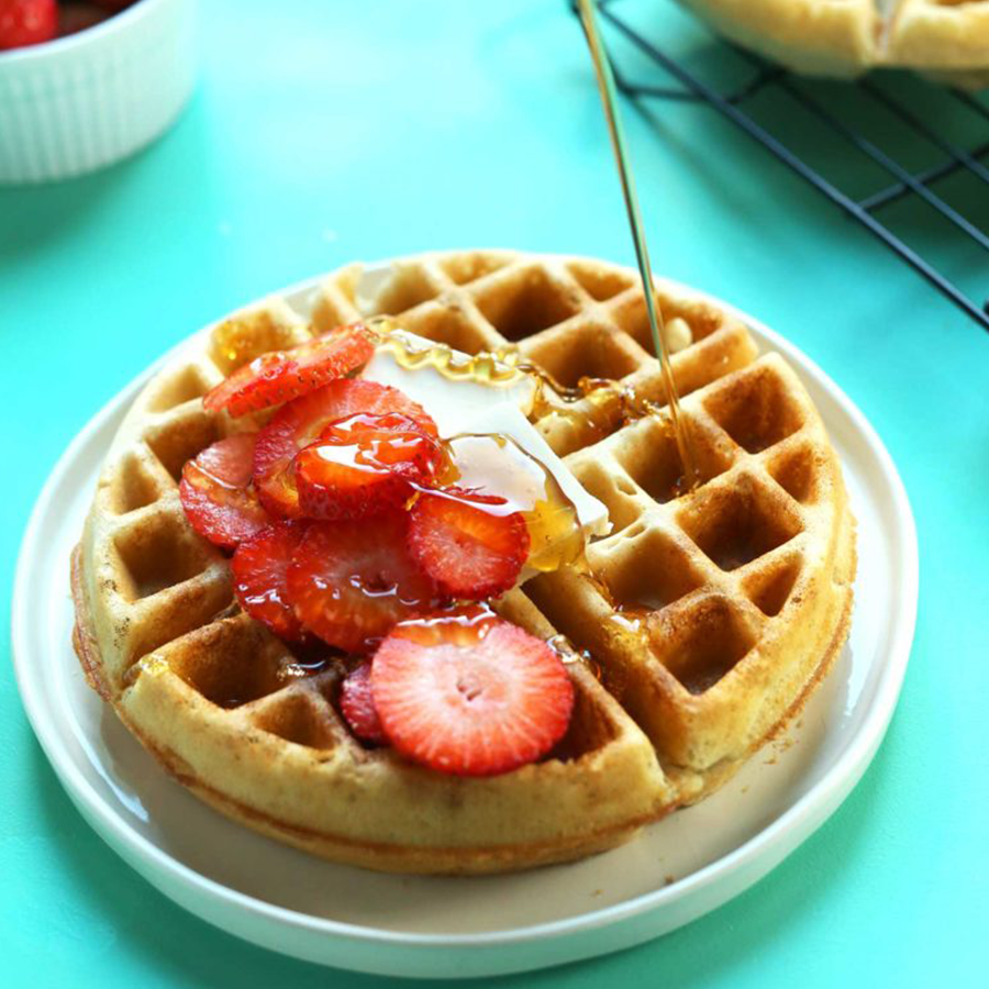 Drizzling syrup onto a homemade Gluten-Free Vegan Waffle for a Mother's Day Recipe Idea