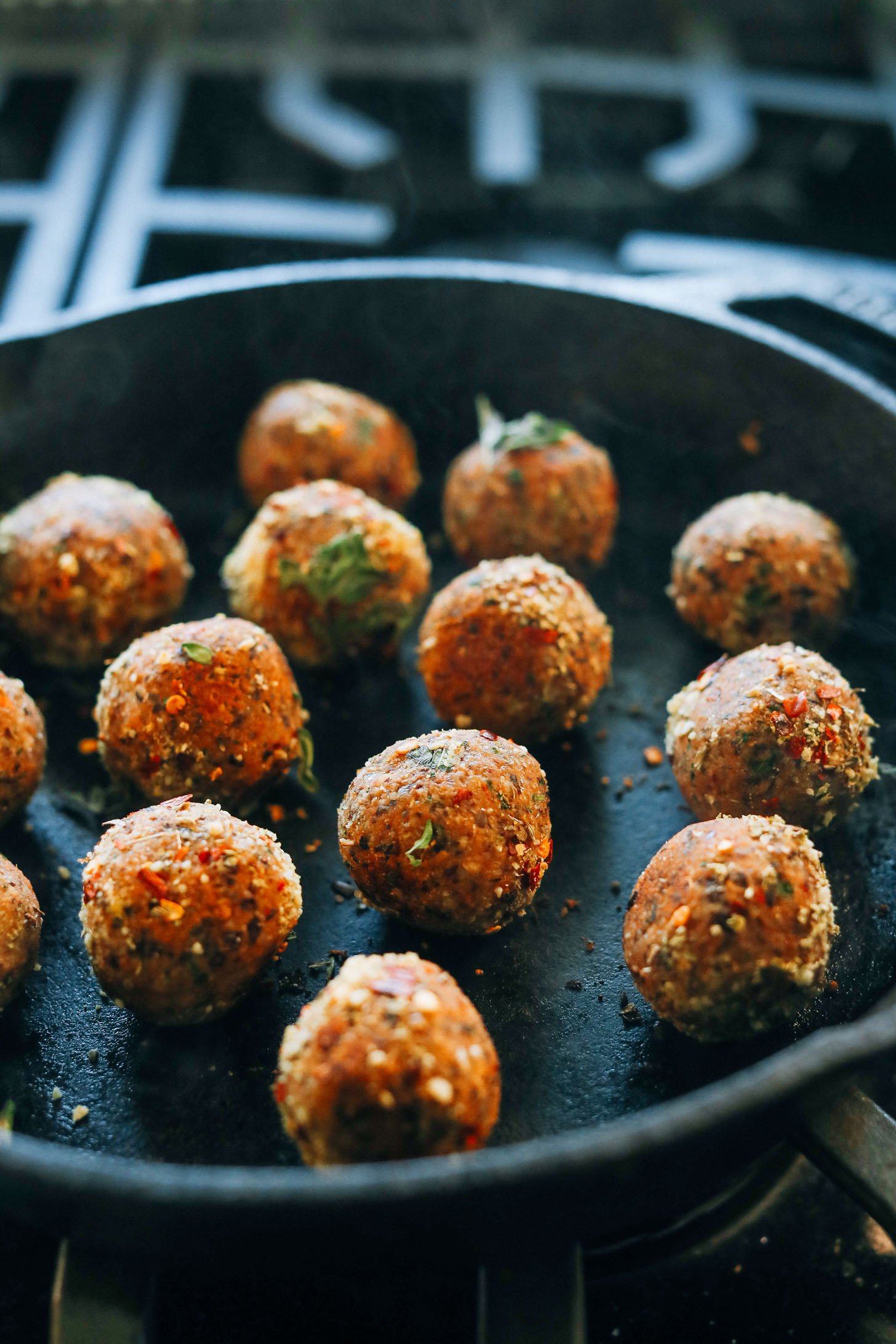 Browning vegan meatballs in a cast-iron skillet