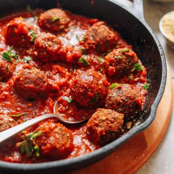Cast-iron skillet filled with a batch of our delicious vegan meatball recipe