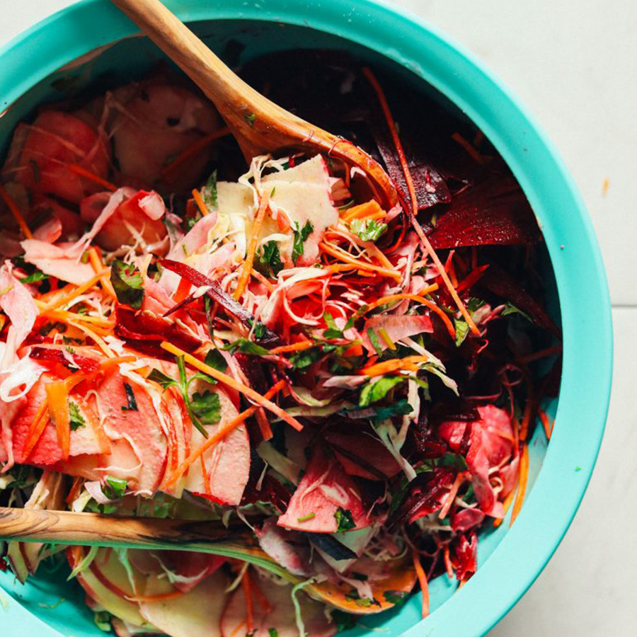 Wooden salad spoons in a big bowl of our Vegan Super Cleansing Slaw recipe