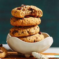 Stack of Vegan Trail Mix Cookies in a bowl with scooped sides