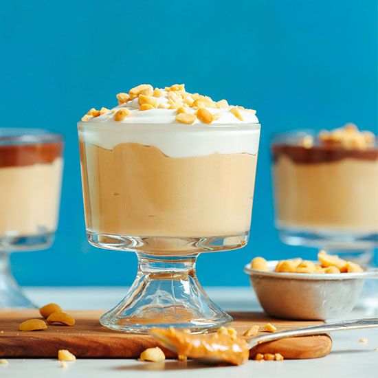 Glass dishes filled with Vegan Peanut Butter Pudding topped with coconut whipped cream and chopped peanuts