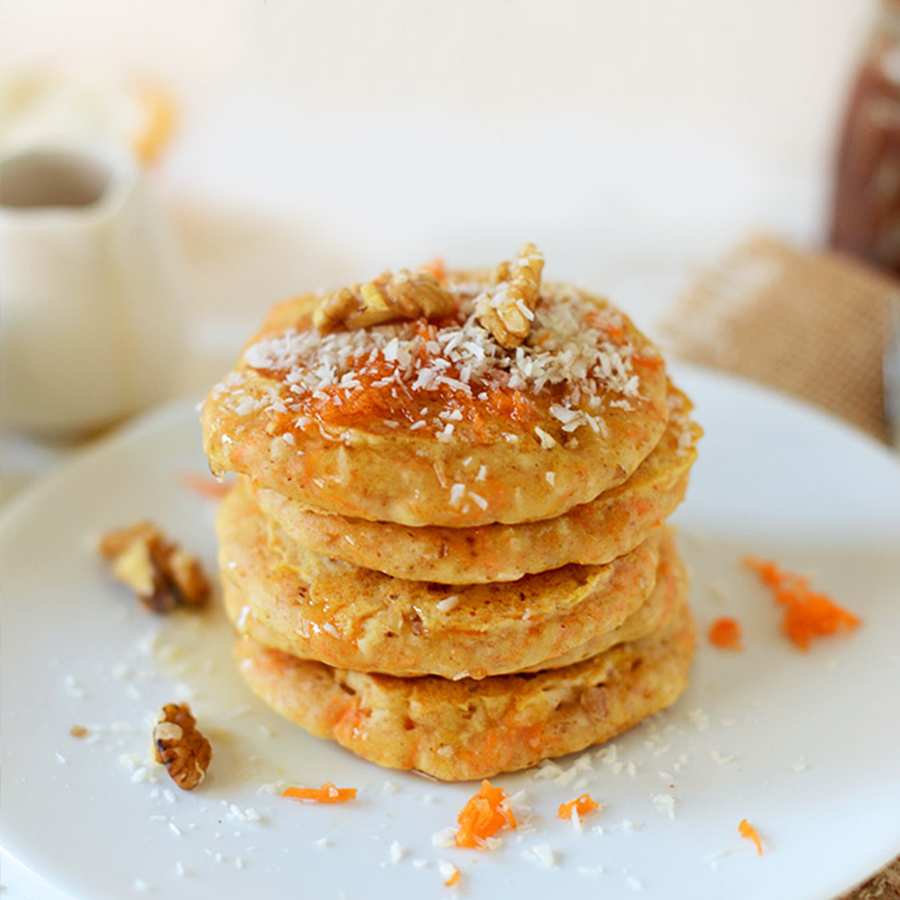 Stack of Carrot Pancakes topped with shredded coconut and walnuts for our Easy Plant-Based Mother's Day Recipes roundup
