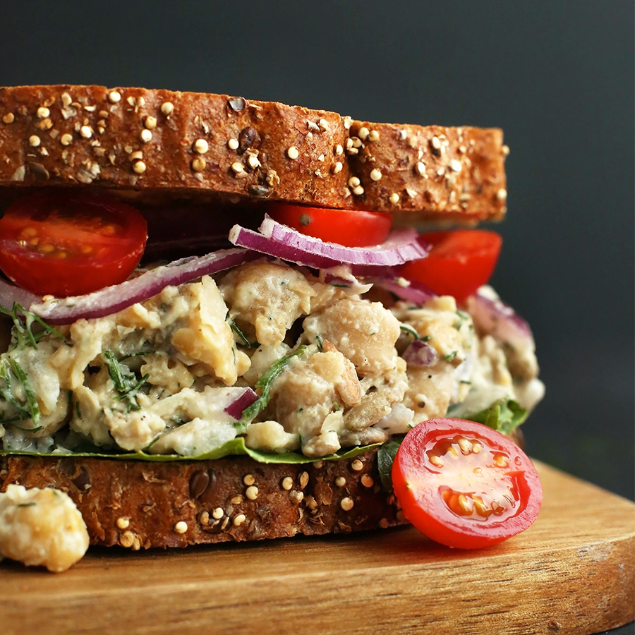 Cutting board with a Chickpea Sunflower Sandwich perfect for taking on a road trip