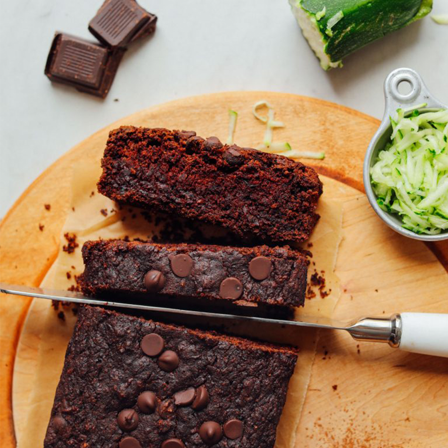 Cutting board with dark chocolate squares, grated zucchini, and a partially sliced loaf of Chocolate Chip Zucchini Bread