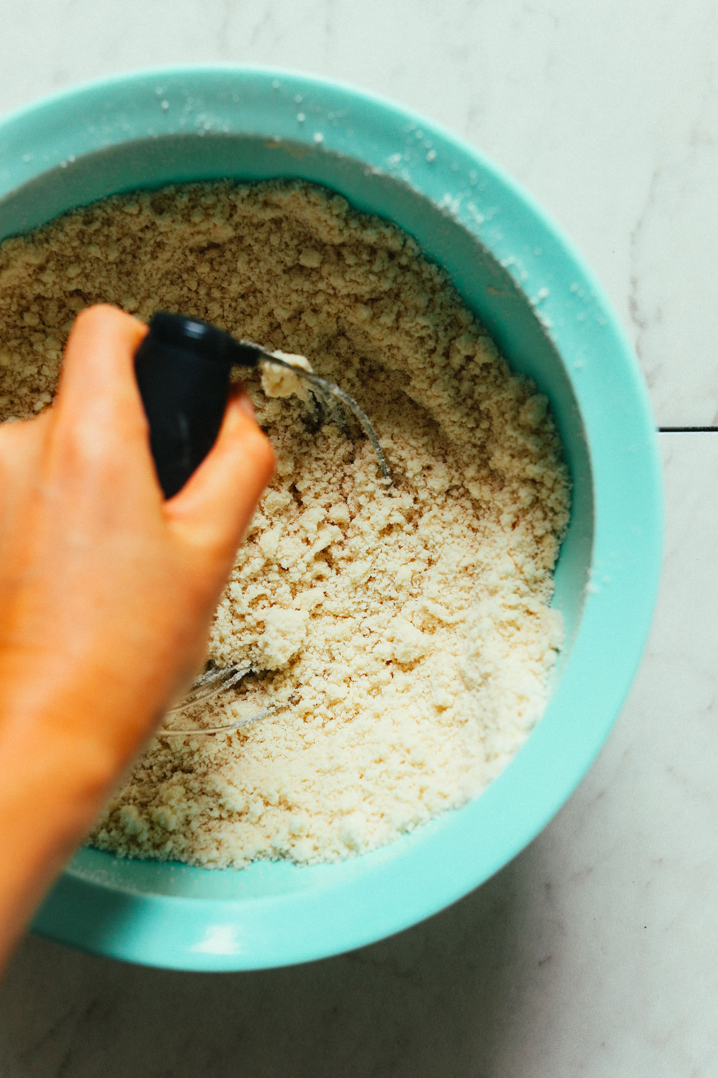 Using a pastry cutter to mix cinnamon roll ingredients