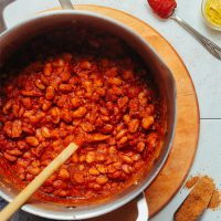 Using a wooden spoon to stir a pot of our simple 1-Pot BBQ Baked Beans recipe