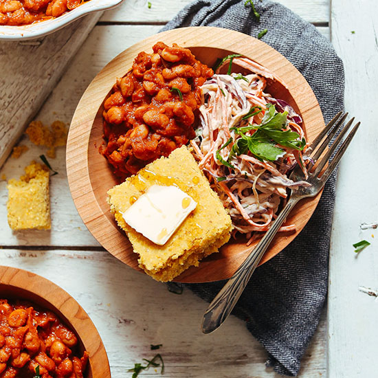 Wood bowl of our Vegan BBQ Bowl with Baked Beans, Coleslaw, and GF Cornbread