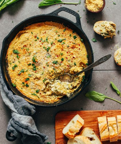 Cast-iron skillet filled with delicious vegan GF Spinach Artichoke Dip
