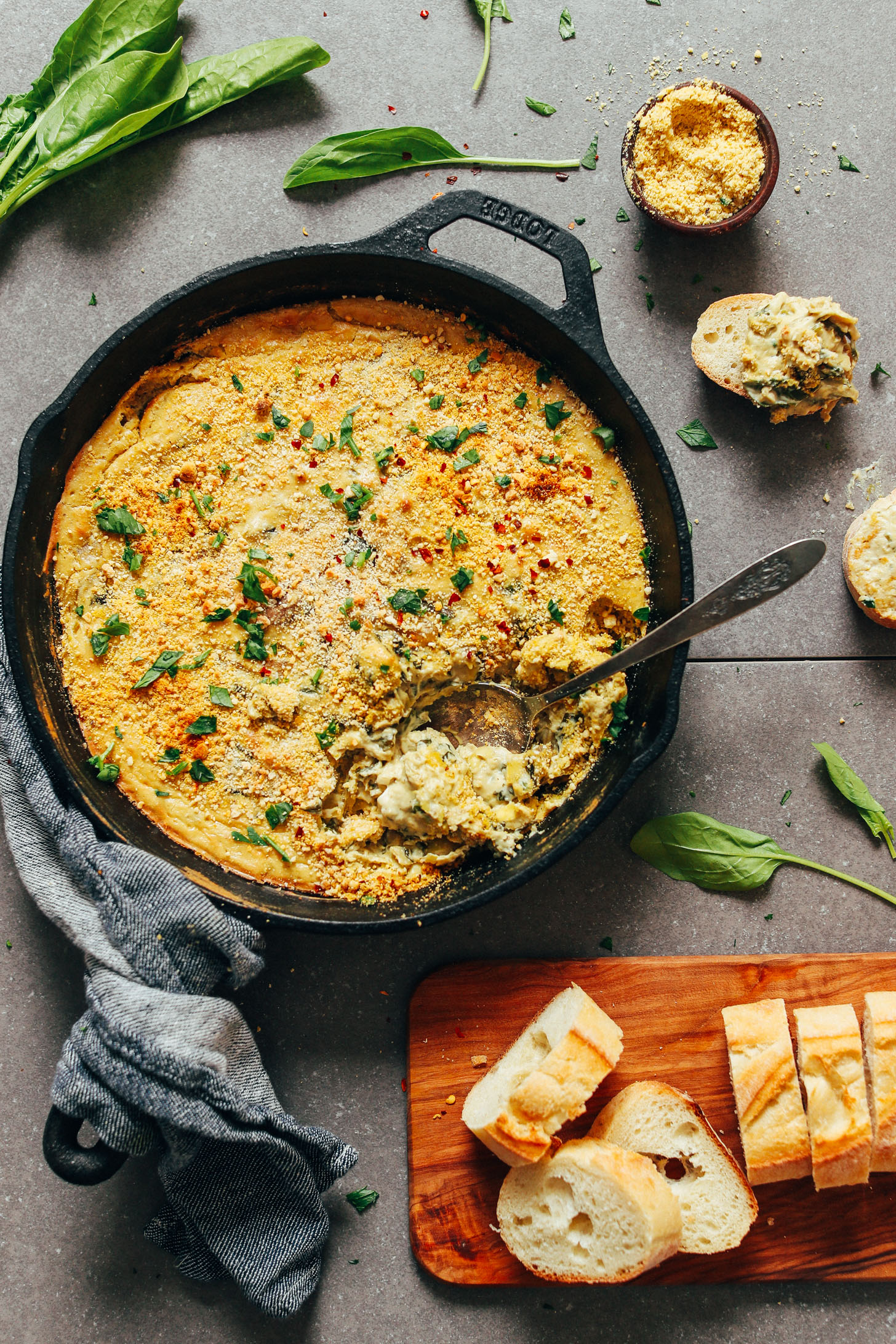 Spoon submerged in a skillet of homemade vegan GF Spinach Artichoke Dip