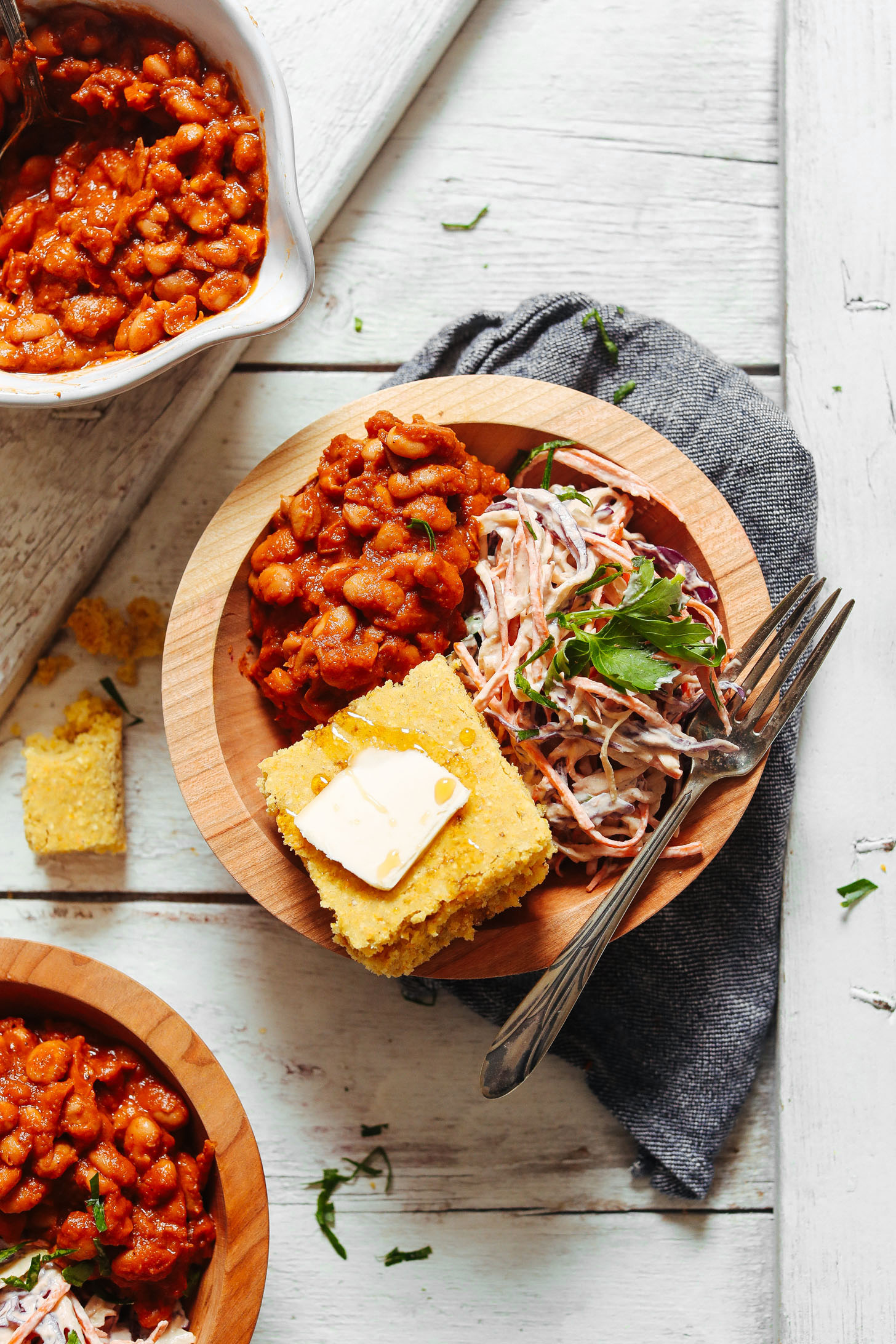 Close up shot of a bowl of Baked Beans, Vegan Coleslaw, and GF Cornbread with Vegan Butter