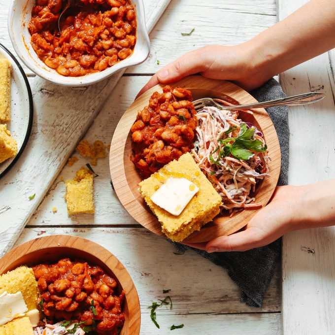 Holding a BBQ Bowl with Baked Beans, Vegan Coleslaw, and GF Cornbread