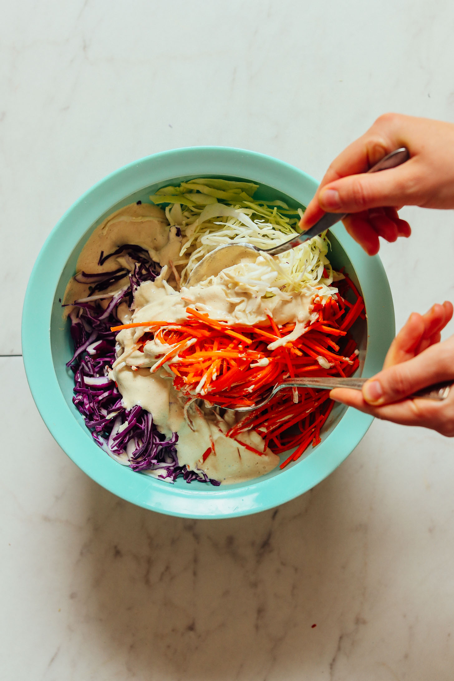 Using serving spoons to toss together vegetables and dressing for vegan coleslaw