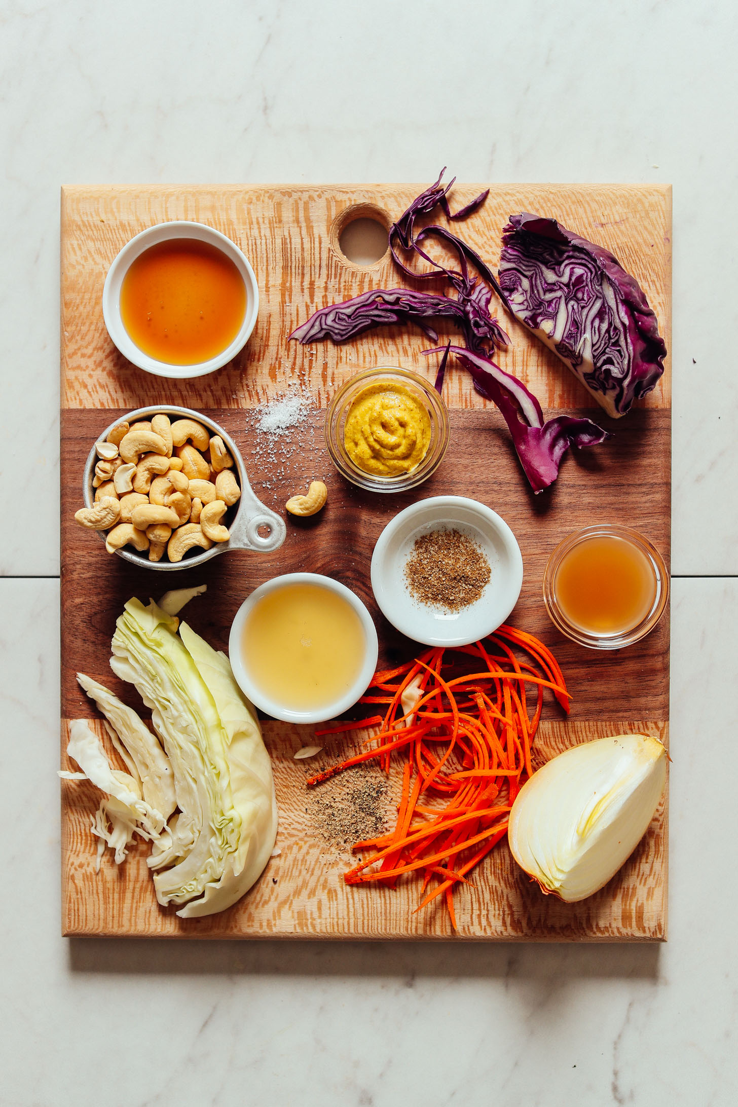 Cutting board filled with ingredients for making our healthy homemade vegan coleslaw recipe