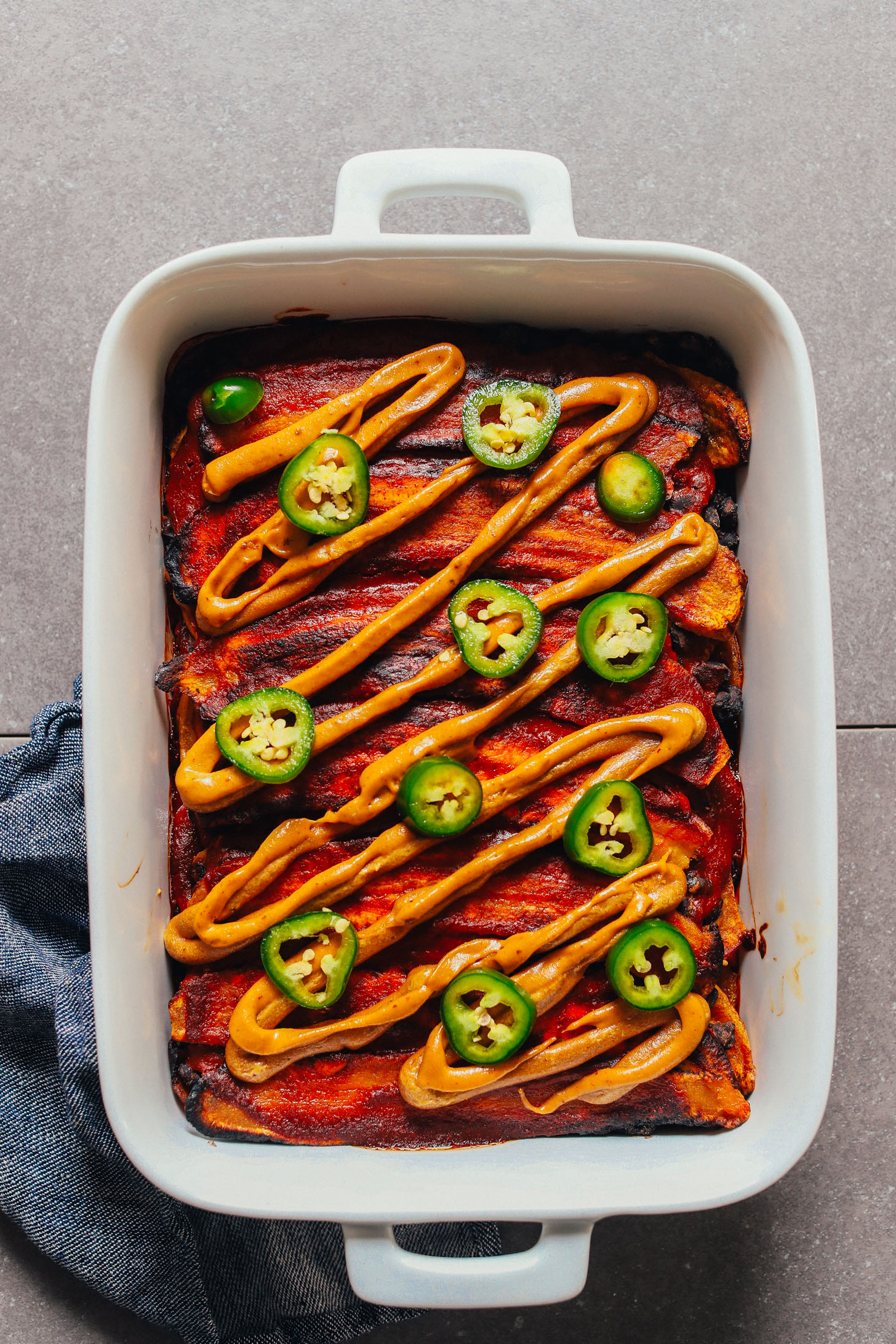 Baking dish filled with our recipe for Plantain Black Bean Enchilada Bake with Vegan Queso