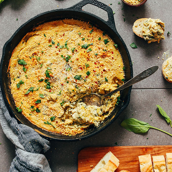 Using a spoon to grab a serving of Creamy Vegan Spinach and Artichoke Dip