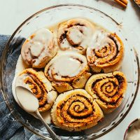 Covering a batch of Vegan Gluten-Free Cinnamon Rolls with icing
