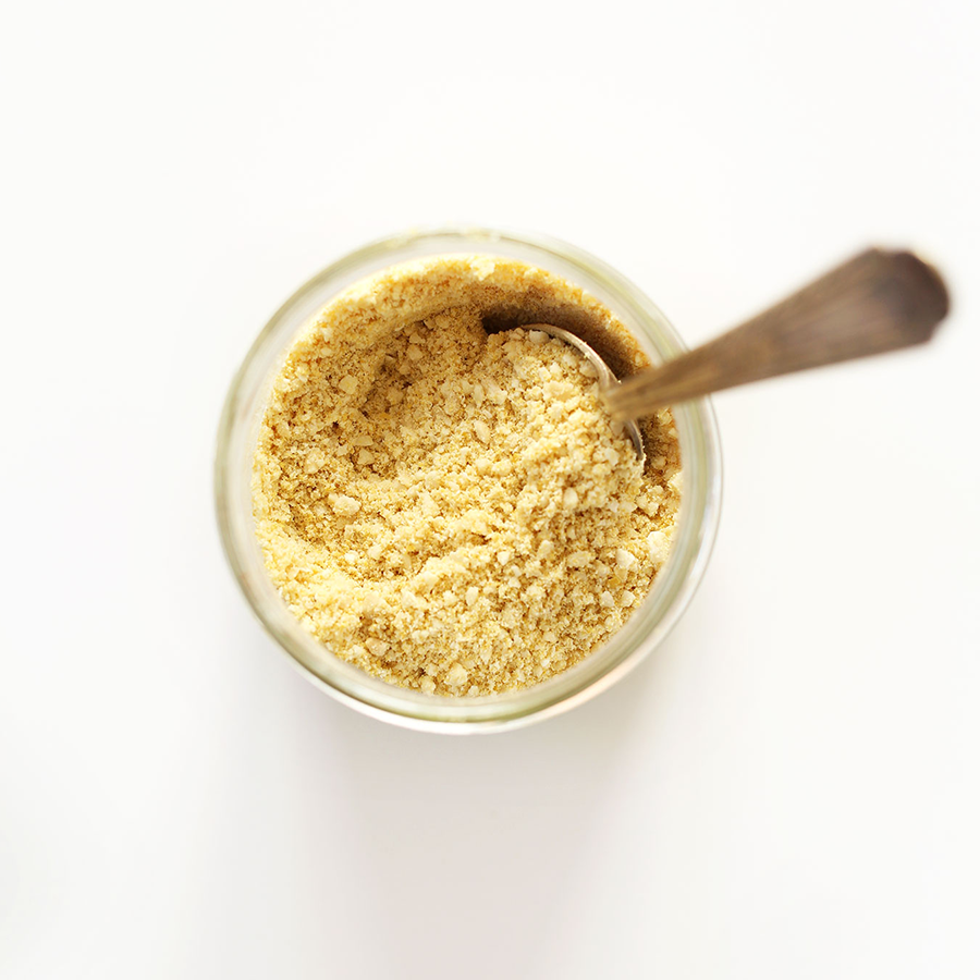 Spoon in a jar of Vegan Parmesan Cheese for our Plant-Based Pizza Night recipe roundup