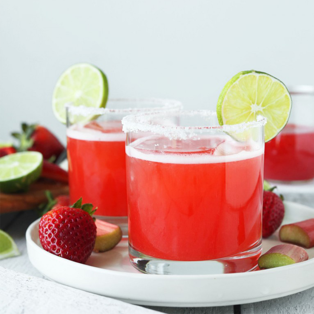 Two glasses of Strawberry Rhubarb Margaritas on a plate for our roundup of Easy Plant-Based Summer Recipes
